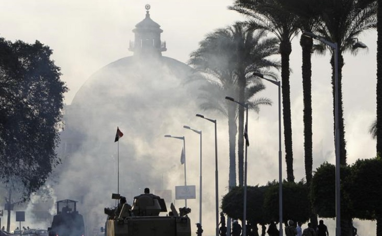 An army vehicle holds position outside Cairo University during clashes between riot policemen and Cairo University students, supporters of Muslim Brotherhood and ousted President Mursi,  in Cairo