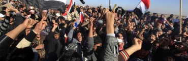Iraqi Sunni Muslims wave Iraqi national flags during an anti-government demonstration in Falluja